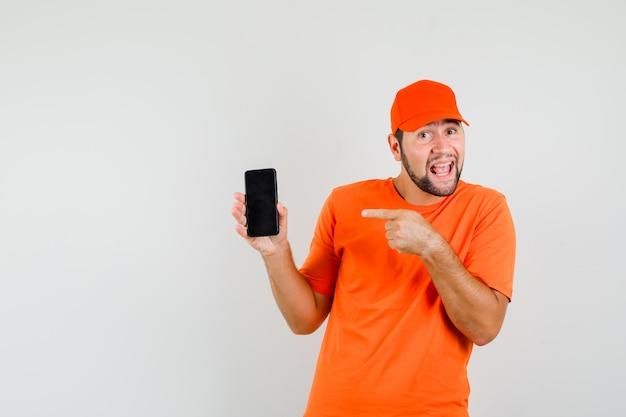 Lieferbote, der auf handy in orangefarbenem t-shirt, mütze zeigt und optimistisch aussieht, vorderansicht.