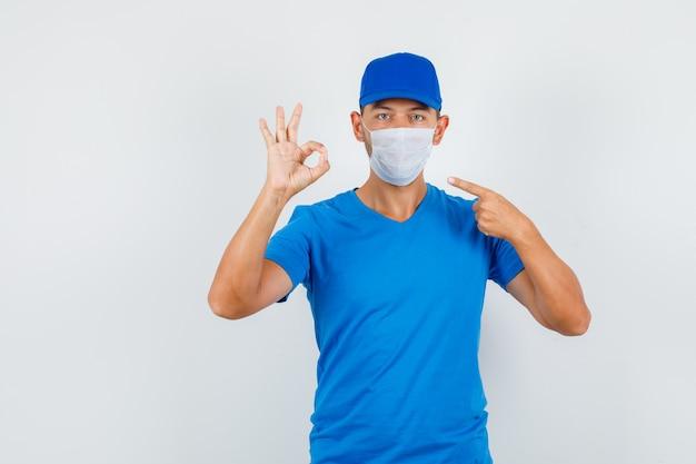 Lieferbote, der auf maske mit ok-zeichen im blauen t-shirt zeigt