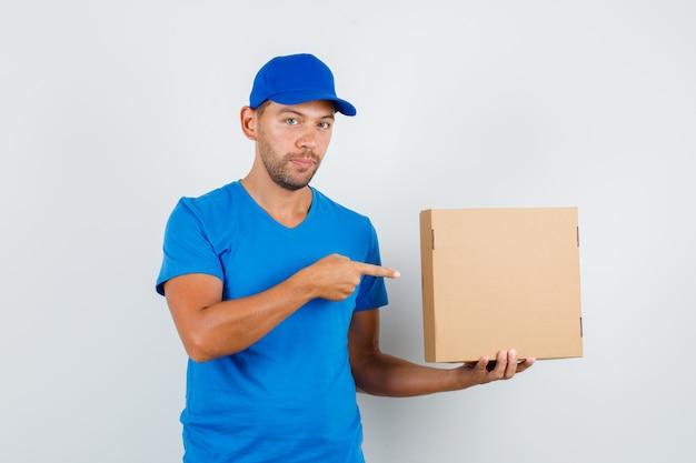 Lieferbote, der auf pappkarton im blauen t-shirt zeigt