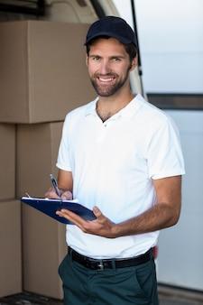 Lieferbote, der auf zwischenablage schreibt, während er neben seinem van steht