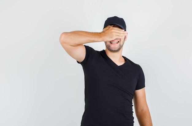 Lieferbote, der augen mit hand im schwarzen t-shirt, in der kappe bedeckt und fröhlich schaut.