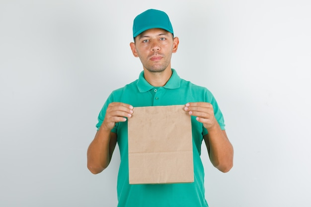 Lieferbote, der braune papiertüte im grünen t-shirt mit kappe hält