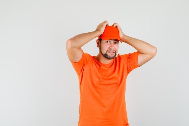 Lieferbote, der die hände am kopf in orangefarbenem t-shirt, mütze hält und verwirrt aussieht, vorderansicht.