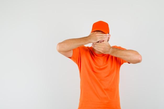 Lieferbote, der die hände auf augen und mund in orangefarbenem t-shirt, mütze und angst hält, vorderansicht.