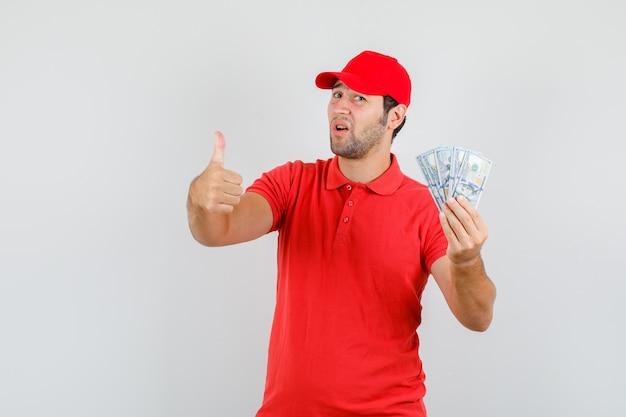 Lieferbote, der dollarbanknoten mit daumen oben im roten t-shirt hält