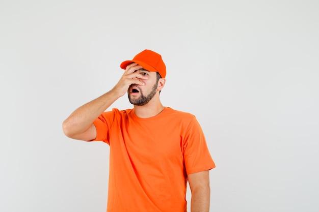 Lieferbote, der durch die finger in orangefarbenem t-shirt, mütze schaut und vergesslich aussieht, vorderansicht.