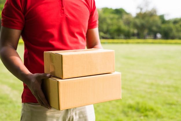 Lieferbote, der ein kastenpaket hält