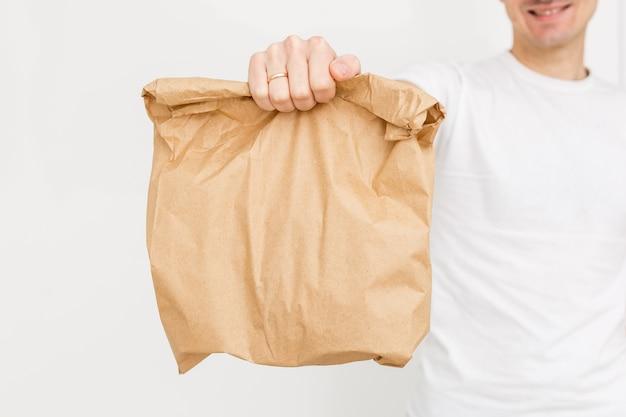 Lieferbote, der eine papiertüte und ein klemmbrett lokalisiert auf weißem hintergrund hält
