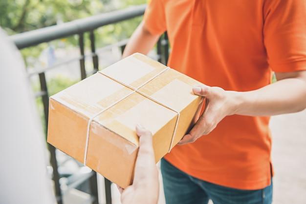 Lieferbote, der einem kunden einen paketkasten gibt