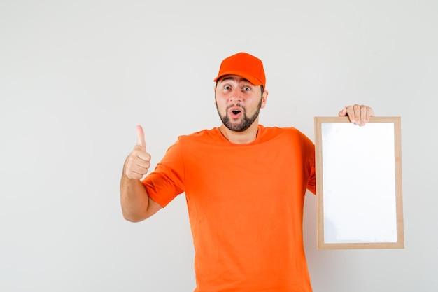 Lieferbote, der einen leeren rahmen mit dem daumen nach oben im orangefarbenen t-shirt, in der mütze hält und glücklich aussieht, vorderansicht.