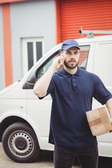 Lieferbote, der einen telefonanruf beim halten eines pakets macht