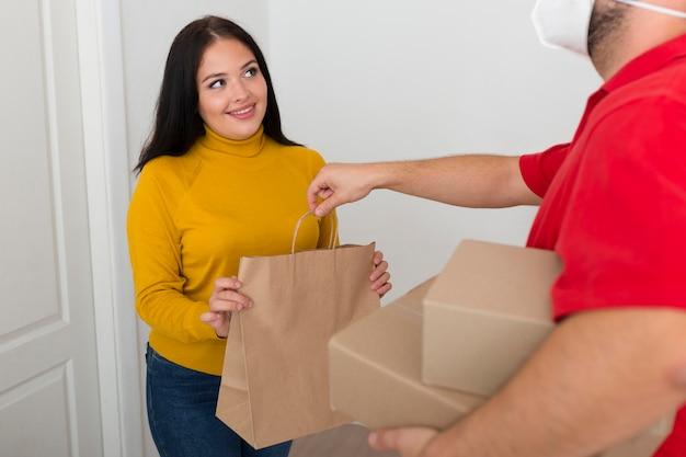 Lieferbote, der einer frau ihren neukauf gibt