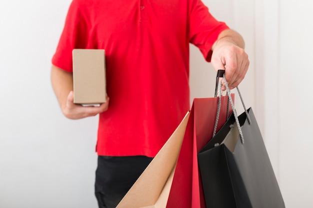 Lieferbote, der einkaufstaschen hält