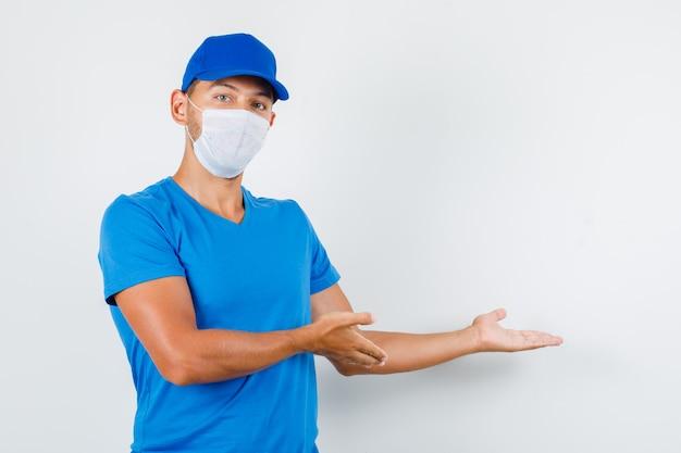 Lieferbote, der etwas im blauen t-shirt begrüßt oder zeigt