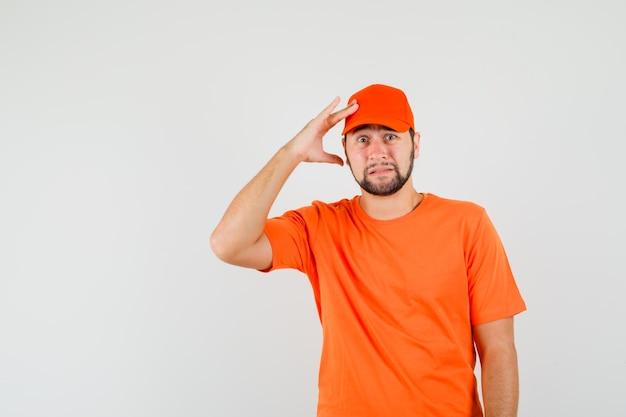 Lieferbote, der finger auf dem kopf in orangefarbenem t-shirt, mütze hält und beunruhigt aussieht. vorderansicht.