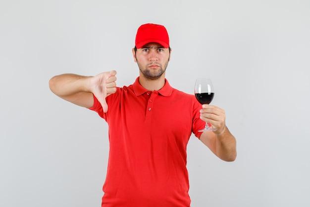 Lieferbote, der glas alkohol mit daumen nach unten im roten t-shirt hält