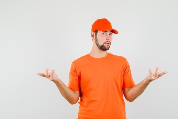 Lieferbote, der hände hält und verwirrte geste in orangefarbenem t-shirt, mütze, vorderansicht zeigt.