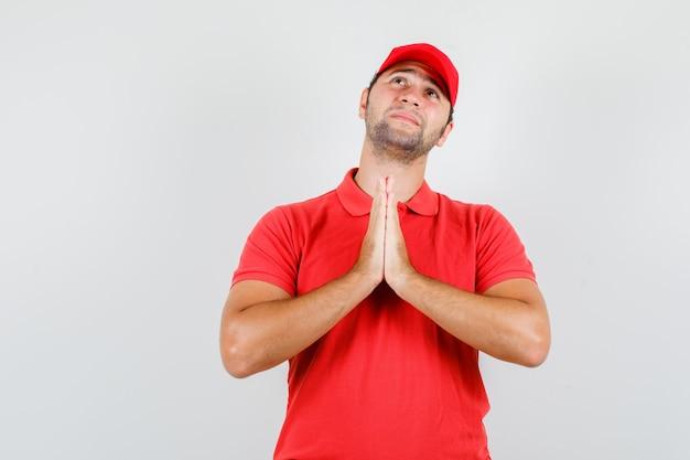 Lieferbote, der hände in der gebetsgeste im roten t-shirt hält