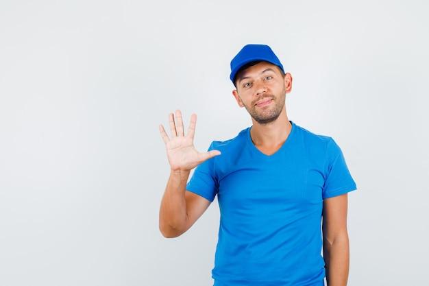 Lieferbote, der handfläche im blauen t-shirt zeigt
