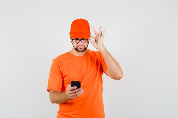 Lieferbote, der handy durch eine brille in orangefarbenem t-shirt, mütze, vorderansicht betrachtet.