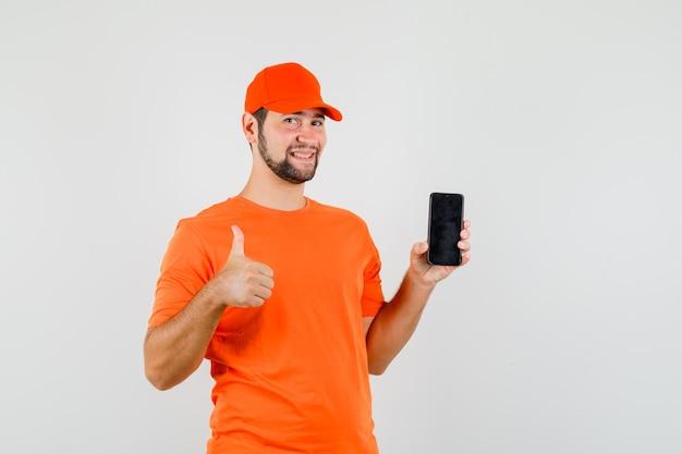 Lieferbote, der handy mit daumen nach oben in orangefarbenem t-shirt, mütze hält und fröhlich aussieht, vorderansicht.