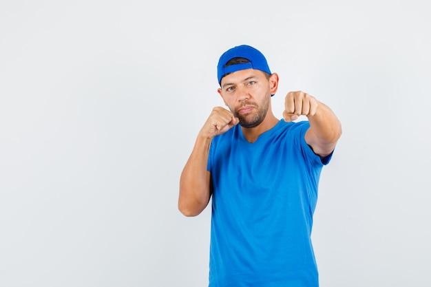Lieferbote, der in der boxerhaltung im blauen t-shirt steht
