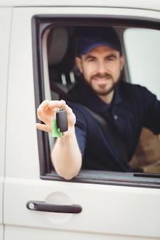 Lieferbote, der in seinem packwagen beim halten von schlüsseln sitzt