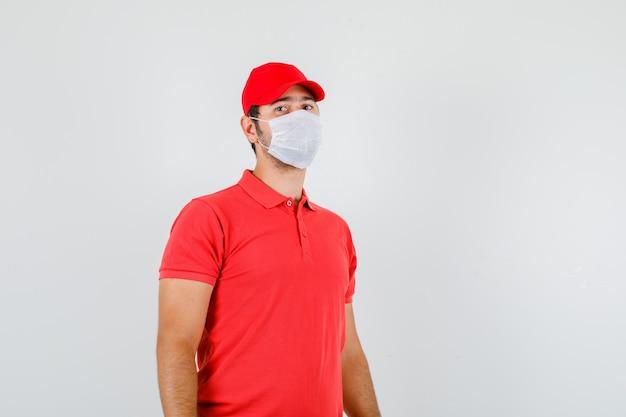 Lieferbote, der kamera im roten t-shirt betrachtet