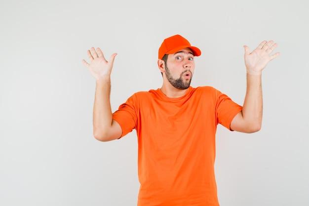 Lieferbote, der kapitulationsgeste in orangefarbenem t-shirt, mütze, vorderansicht zeigt.