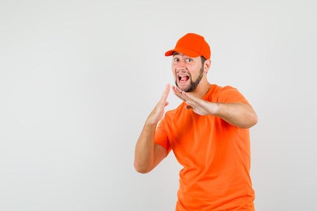 Lieferbote, der karate-chop-geste in orangefarbenem t-shirt, mütze zeigt und mächtig aussieht. vorderansicht.