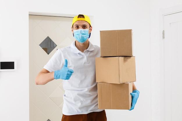 Lieferbote, der kartons in medizinischen gummihandschuhen und maske hält. platz kopieren. schneller und kostenloser liefertransport. online-shopping und express-lieferung. quarantäne