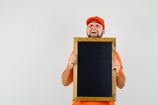 Lieferbote, der leere tafel im orangefarbenen t-shirt, in der mütze hält und fröhlich aussieht. vorderansicht.