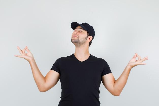 Lieferbote, der meditation mit geschlossenen augen im schwarzen t-shirt, in der mütze und im entspannten blick tut.