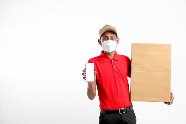 Lieferbote, der medizinische maske trägt und smartphone-bildschirm mit box in den händen zeigt. hauslieferung. online-technologie bestellen.