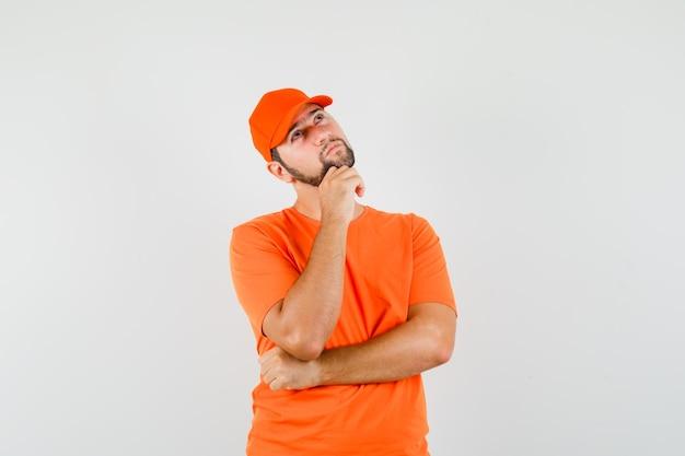 Lieferbote, der mit der hand am kinn in orangefarbenem t-shirt, mütze und nachdenklich schaut. vorderansicht.