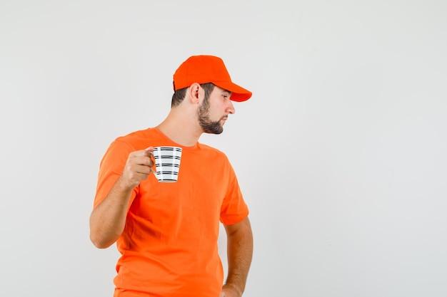 Lieferbote, der mit einer tasse getränk in orangefarbenem t-shirt, mütze und nachdenklichem blick beiseite schaut, vorderansicht.