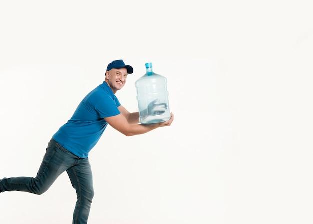 Lieferbote, der mit wasserflasche lächelt und aufwirft