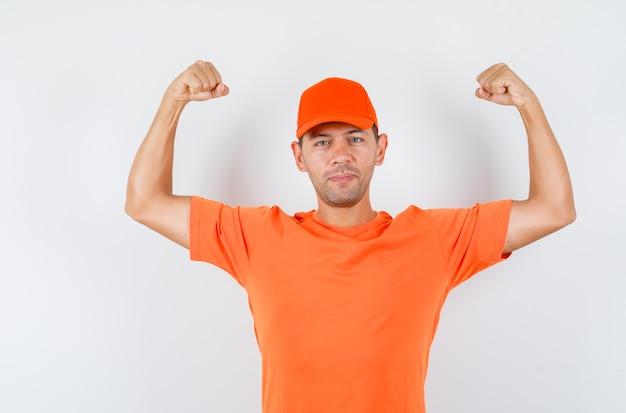 Lieferbote, der muskeln der arme im orangefarbenen t-shirt und in der mütze zeigt und stark schaut
