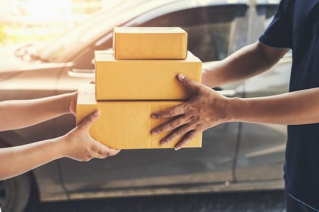 Lieferbote, der paketkasten halten an kunden liefert