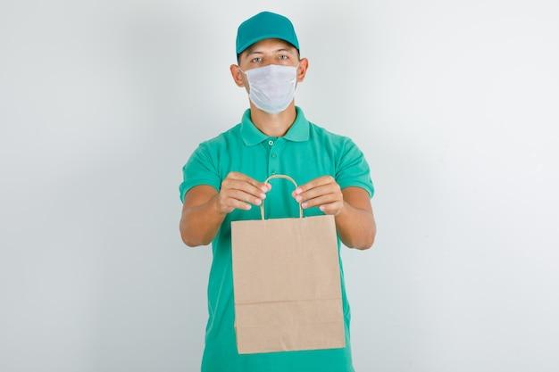 Lieferbote, der papiertüte im grünen t-shirt mit kappe und maske hält