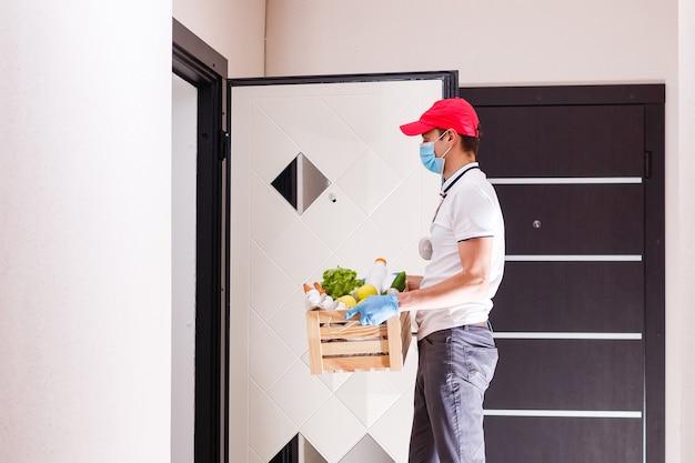 Lieferbote, der papiertüte mit essen auf weißem eingang des haushintergrundes hält, essenslieferant in schutzmaske