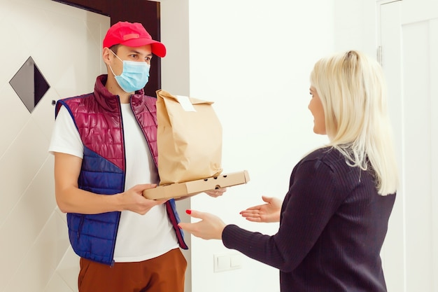 Lieferbote, der papiertüte mit essen auf weißem hintergrund hält, lieferbote in schutzmaske