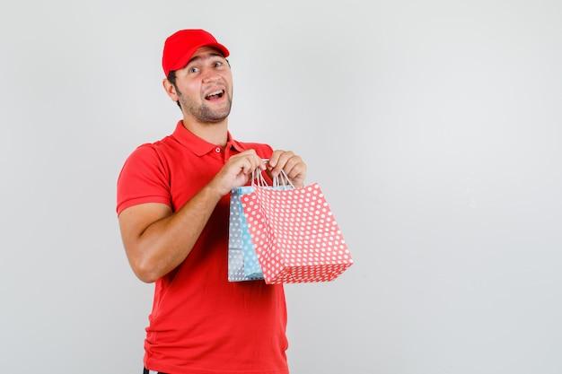 Lieferbote, der papiertüten im roten t-shirt hält