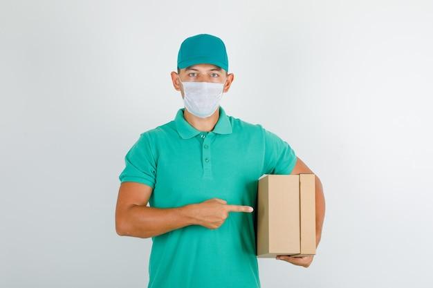 Lieferbote, der pappkarton im grünen t-shirt mit kappe und maske hält