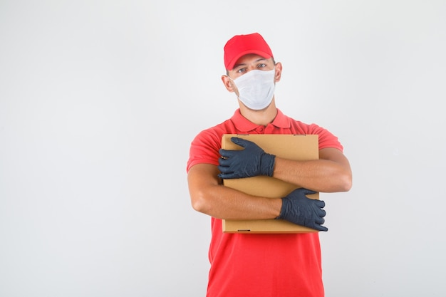 Lieferbote, der pappkarton in roter uniform, medizinischer maske, handschuhen umarmt und selbstbewusst aussieht