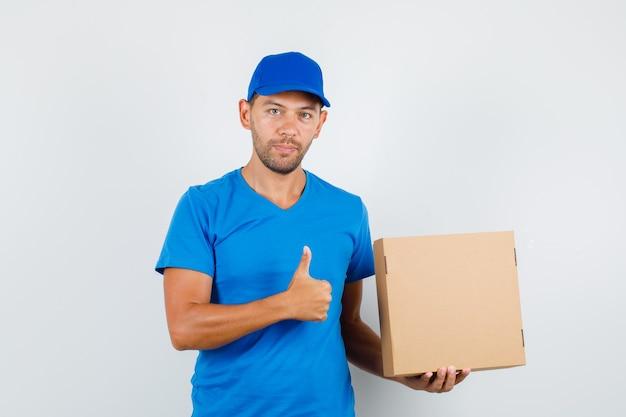 Lieferbote, der pappkarton mit daumen oben im blauen t-shirt hält