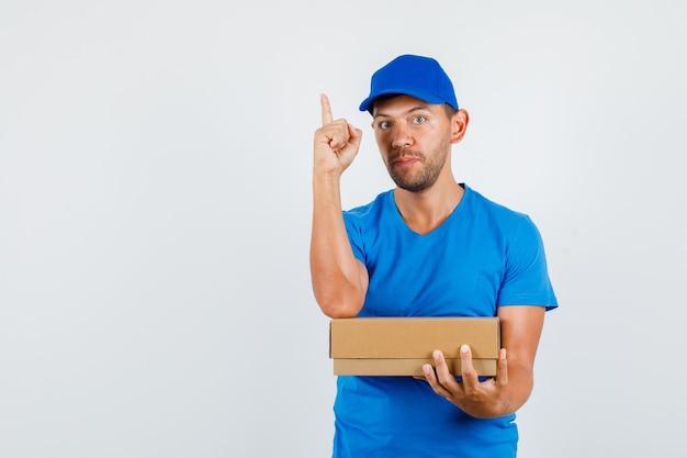 Lieferbote, der pappkarton mit finger oben im blauen t-shirt hält