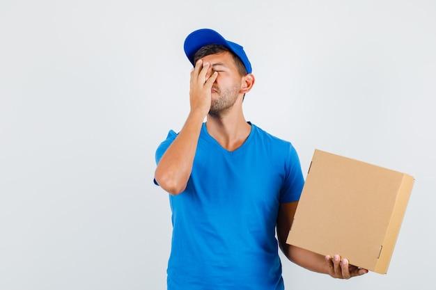 Lieferbote, der pappkarton mit hand auf gesicht im blauen t-shirt hält