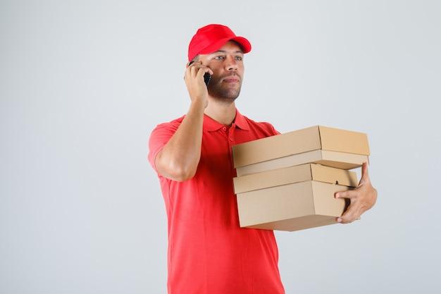 Lieferbote, der pappkartons hält, während auf handy in roter uniform sprechen
