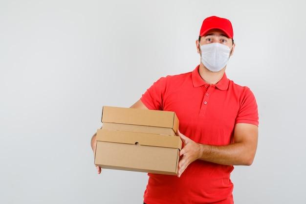 Lieferbote, der pappkartons im roten t-shirt hält